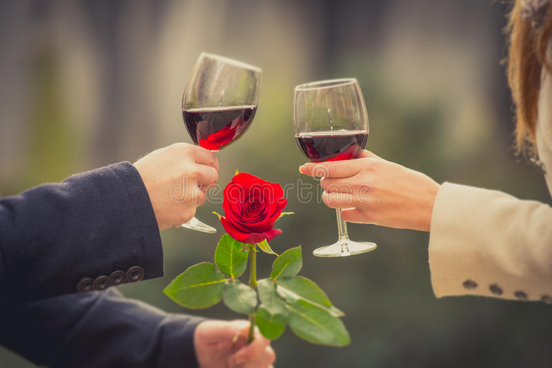 Close up of a couple drinking wine on valentines day. Close up a romantic couple drinking wine with a rose in the mans hand on valentines day