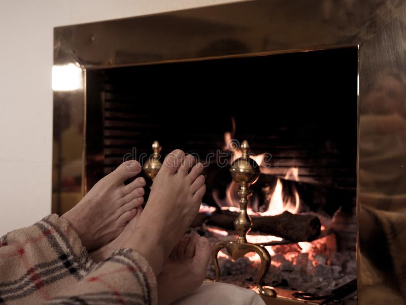 Close up of couple feet warming up by the fireplace in winter vacation and happy moments together stock image