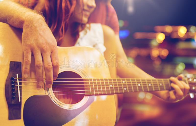 Close up of couple with guitar over night lights. Music, sale, people, musical instruments and entertainment concept - close up of happy couple of musicians royalty free stock photo