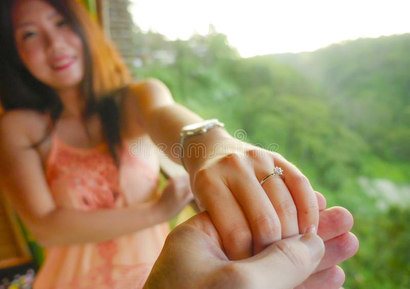 Close up couple hands man holding Asian happy fiance hand with diamond engagement ring on her finger after wedding proposal at. Tropical beautiful and romantic royalty free stock photography