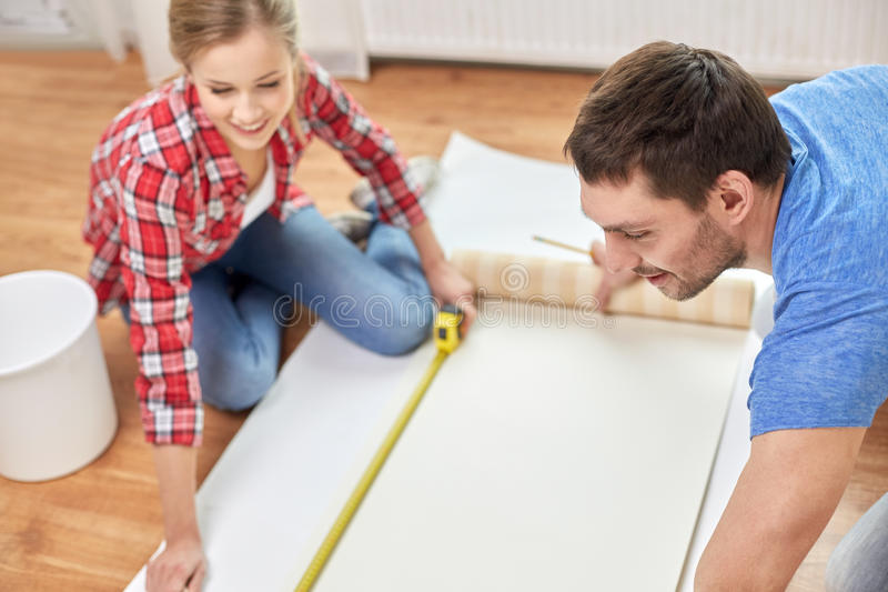 Close up of couple measuring wallpaper. Repair, building and people concept - close up of couple with ruler measuring wallpaper at home royalty free stock image