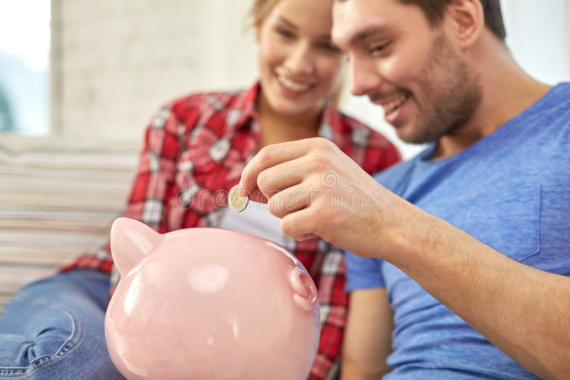 Close up of couple with piggy bank sitting on sofa. Money, home, finance and relationships concept - close up of couple with piggy bank sitting on sofa stock image