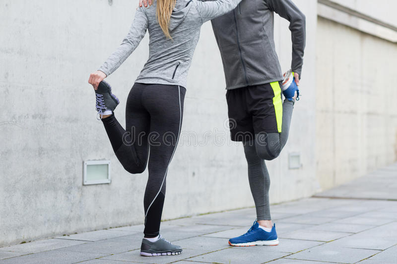 Close up of couple stretching legs outdoors. Fitness, sport, training and lifestyle concept - close up of couple stretching legs outdoors stock images