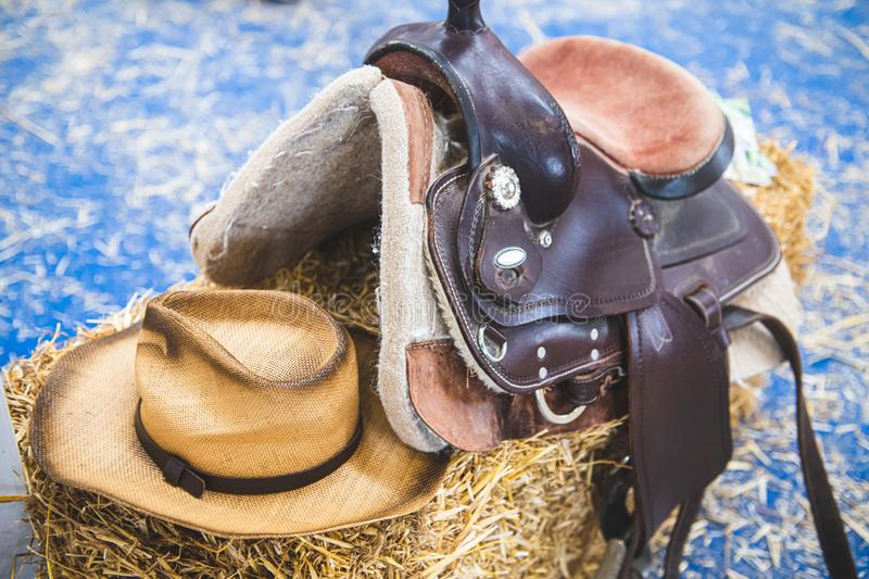 Cowboy horse riding saddle and hat personal equipment. Close-up of cowboy hat and horse saddle in a store on tumbleweed straw bale, american style riding royalty free stock photography