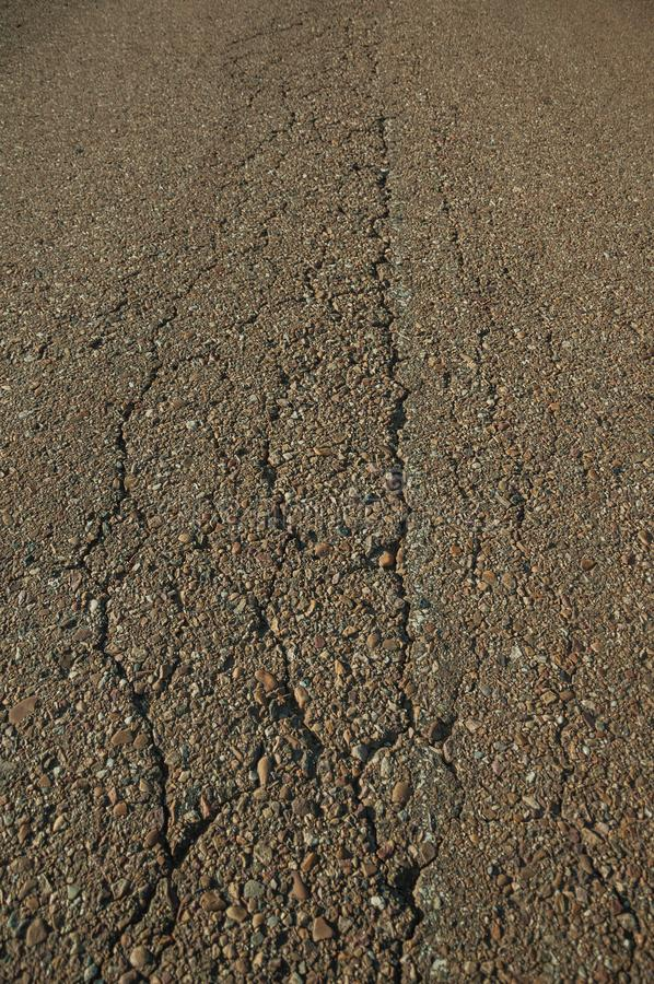 Close-up of cracked asphalt on a road. Close-up of cracked asphalt with small gravel inserted in it, on a countryside road at sunset near Elvas. A gracious star stock photo