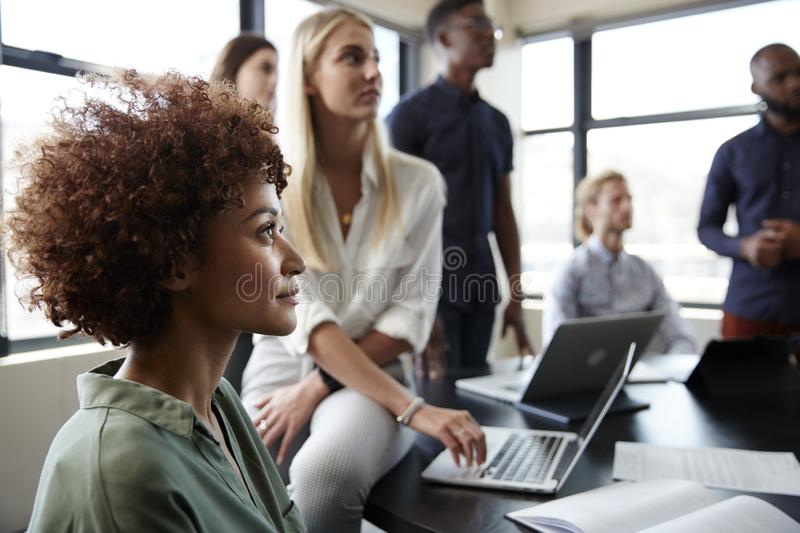 Close up of creative business colleagues listening to an informal presentation in a meeting room royalty free stock photography