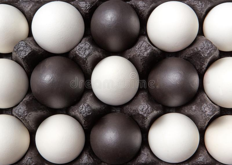 Close-up creative pattern of colored black and white eggs in a black cardboard box. Easter composition. Flat lay royalty free stock photography