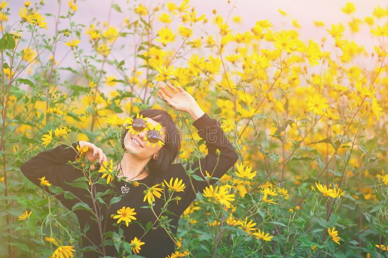 Close up creative portrait of a beautiful young smiling happy brunette girl with yellow flower petals under sunglasses royalty free stock photography