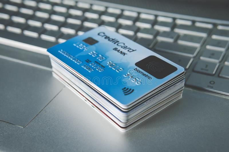 Close up of credit cards set in pile on laptop keyboard. E-commerce concept. Group of credit cards with biometric card on the top. Using fingerprint sensor to royalty free stock photos