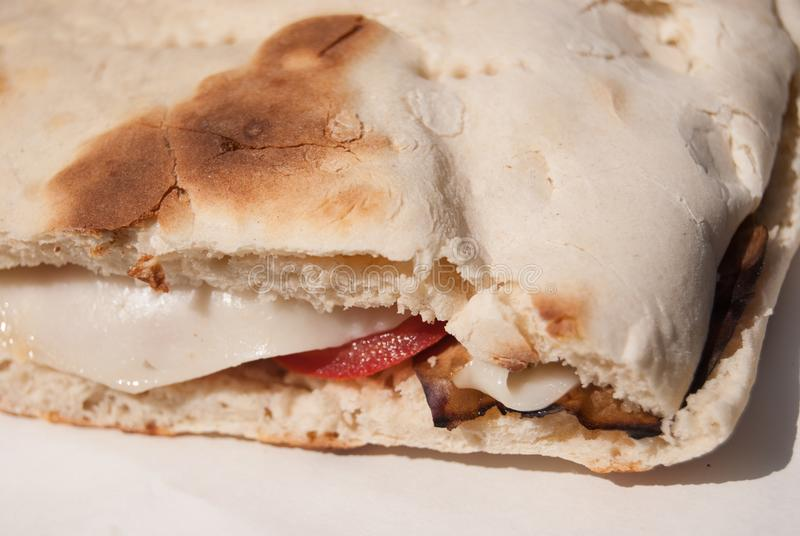 Close up of Crescia typical sandwich of Gubbio. Sandwich with cheese tomatoes and aubergine in the special and characteristic bread royalty free stock images