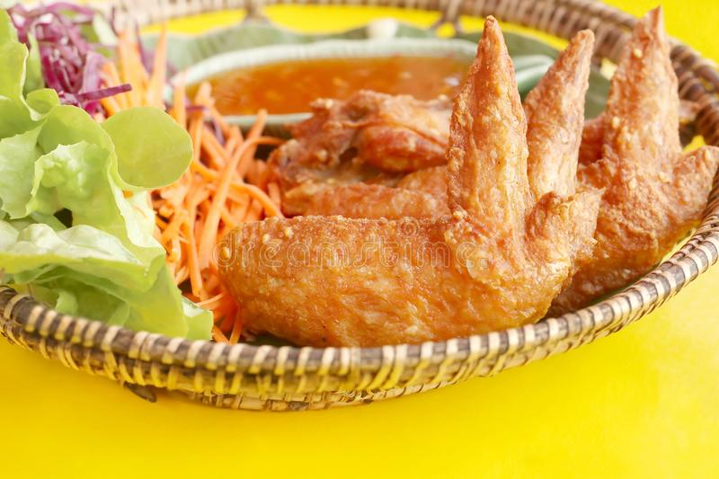 Close up of crispy fried chicken wings with sauce and vegetable salad in bamboo basket on colorful yellow table stock image