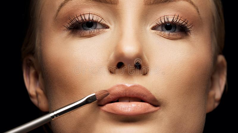 Close up crop of female face applying make up royalty free stock image