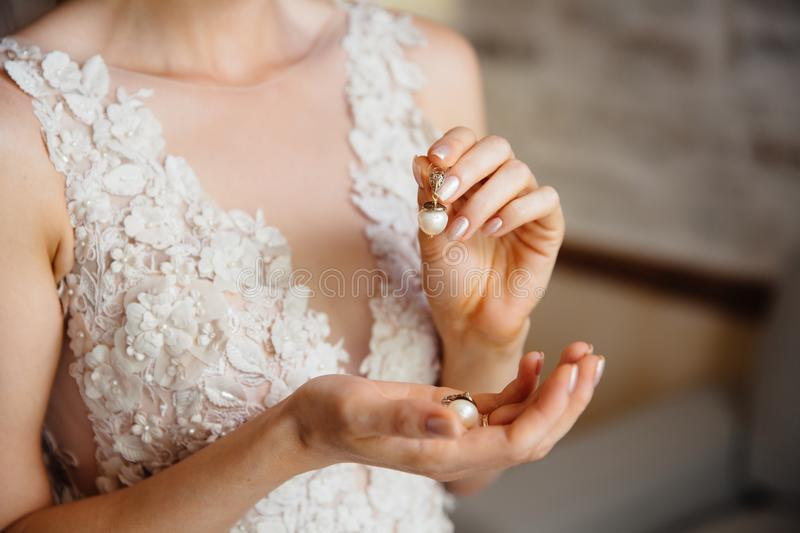 Close-up of a cropped frame of a girl in a white lace dress with embroidery holding in hands a pearl earring. The bride royalty free stock photos