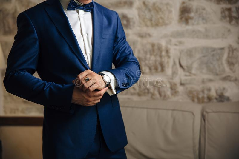 A close-up of a cropped frame of a man in an expensive classic costume looks at his watch. The businessman is in a hurry stock images