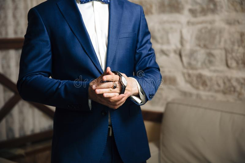 A close-up of a cropped frame of a man puts on a gold watch with a leather belt, is dressed in a stylish suit, a white royalty free stock image