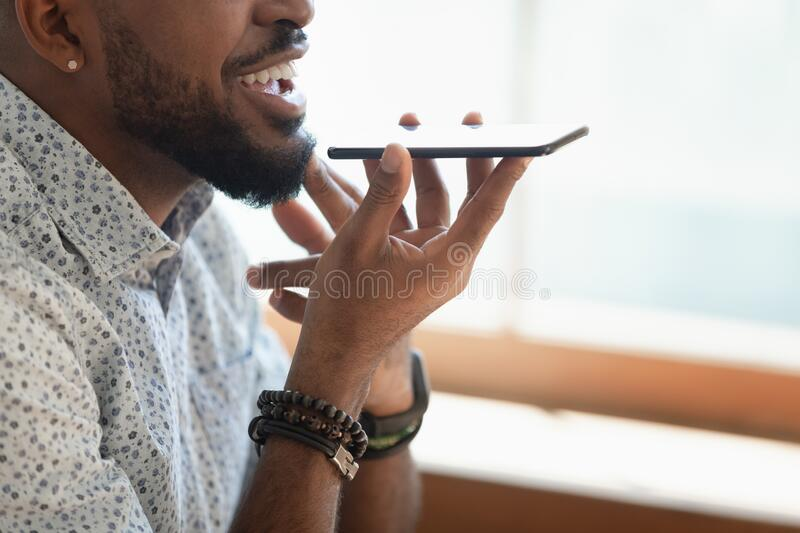 Closeup view african guy talking with friend on speakerphone royalty free stock images