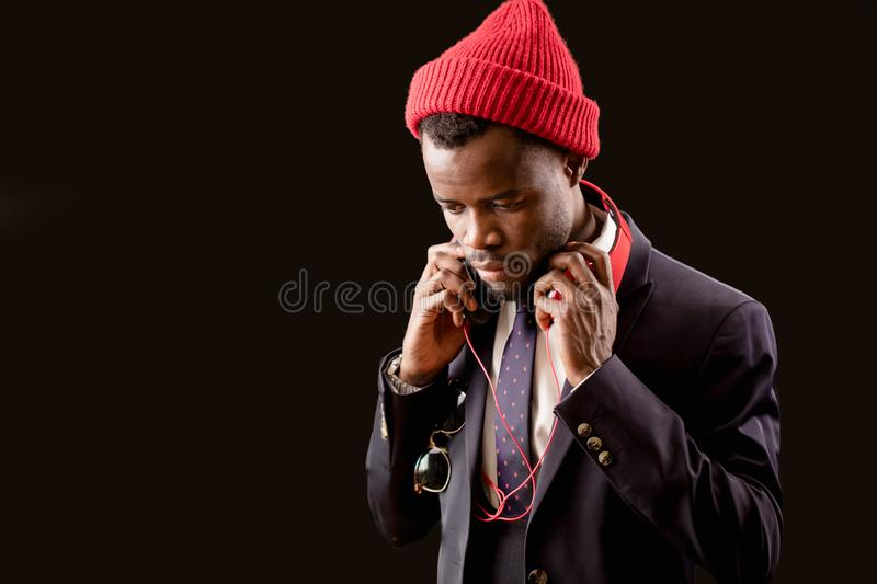 Close up cropped image of Afro rapper wearing red cap. Close up cropped image of serious unshaven Afro rapper wearing red cap isolated on the black background royalty free stock photo
