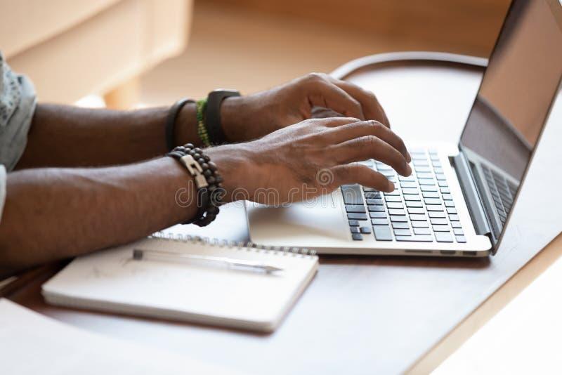 Close up cropped image young black man using laptop. royalty free stock image