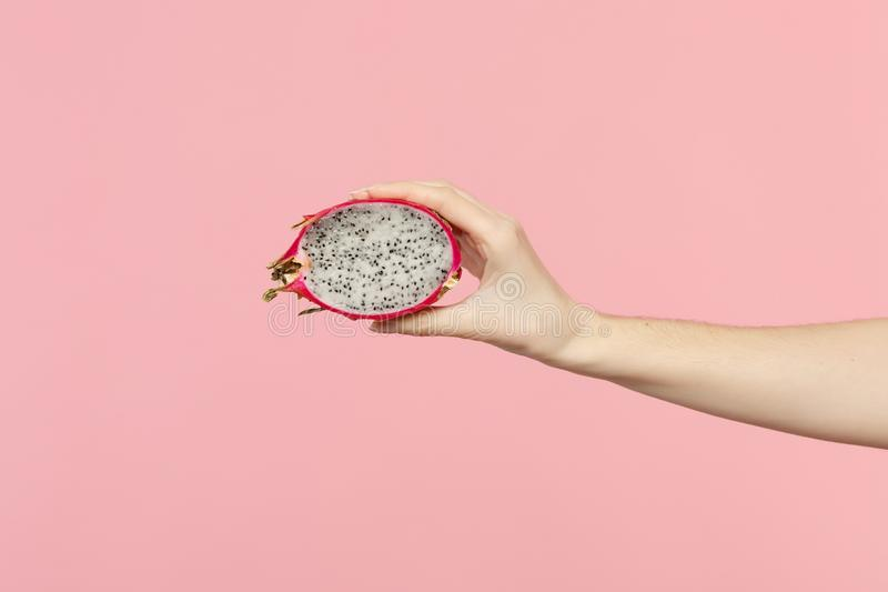 Close up cropped photo of female hold in hand fresh half pitahaya, dragon fruit isolated on pink pastel wall background. Copy space advertising mock up. People royalty free stock photo