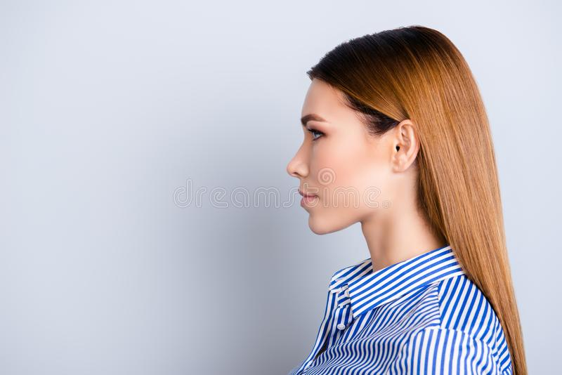 Close up cropped profile portrait of young business lady in striped shirt with serious face on pure background with copy space stock photo