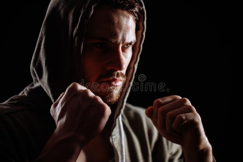 Close up cropped side view photo of handsome man boxing in sporty clothers stock image