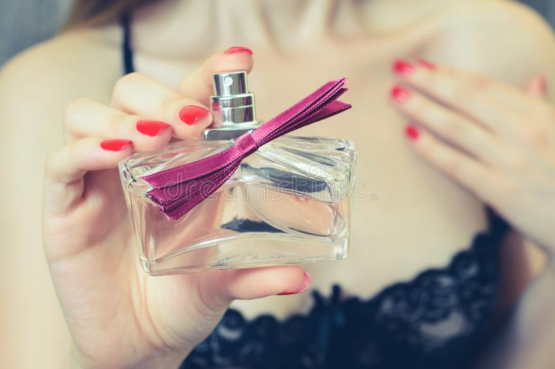 Close up cropped view photo. Woman in seductive clothes showing a bottle of perfume, seductive beautiful attractive sexual wo royalty free stock image