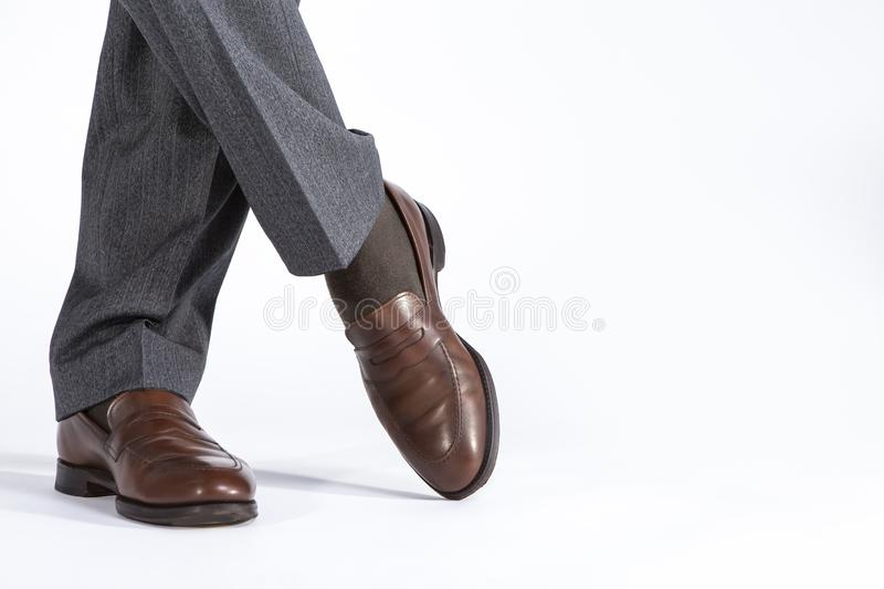Close- up of Crossed Mens Legs Wearing Brown penny Loafers. Against White Background. Horizontal Shot stock images