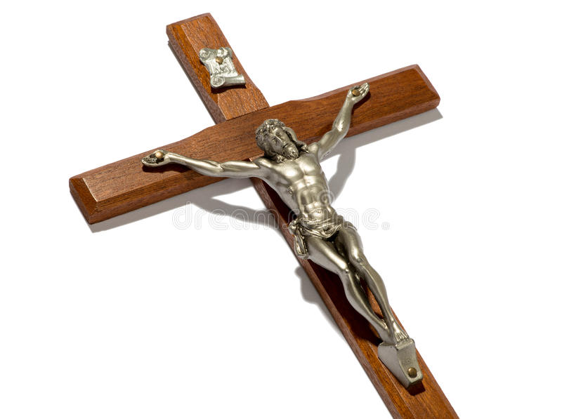 Close up on the crucified figure of Christ. Close up on a silver metallic crucified figure of Christ on a plain wooden cross or crucifix lying at an oblique royalty free stock photo