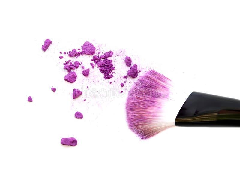 Close up of crushed blush on white background and cosmetic brush. stock image