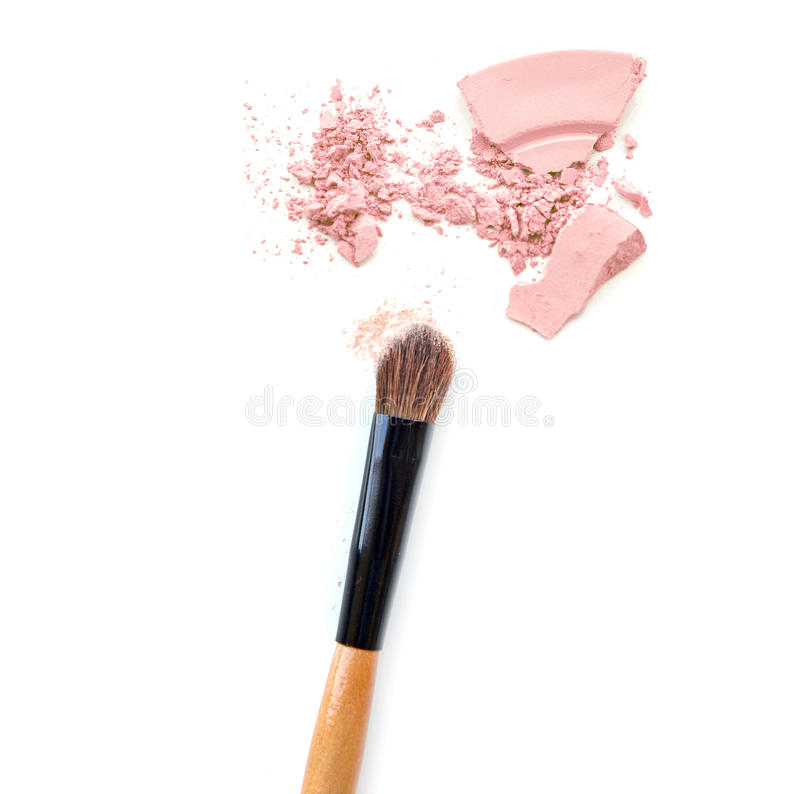 Close-up of crushed mineral shimmer powder golden color with makeup brush on white background. Close-up of crushed mineral shimmer powder golden color with stock images
