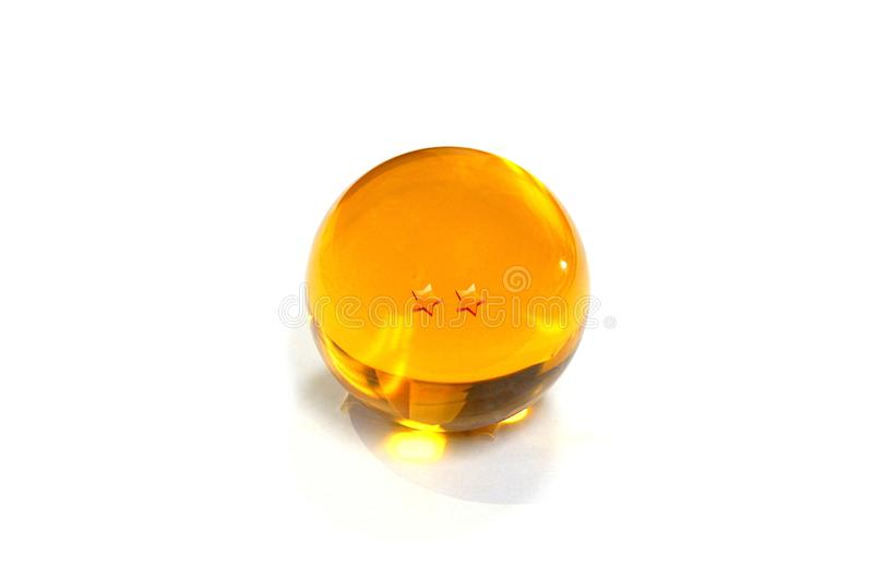 Close-up Crystal Ball yellow with two star on a white background. royalty free stock image