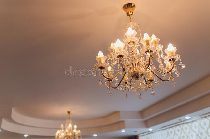 Close up on crystal of contemporary chandelier, is a branched ornamental light fixture designed to be mounted on royalty free stock images