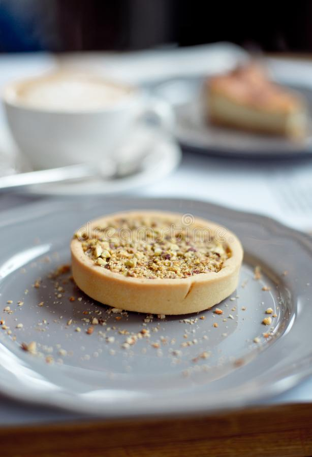 Close-up cup of coffee with pistachio tart on the table.  stock photography