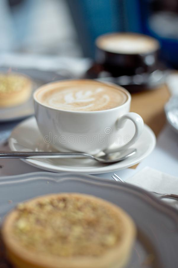 Close-up cup of coffee with pistachio tart on the table.  stock image