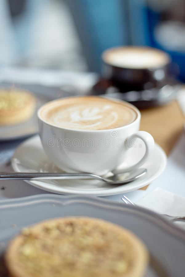 Close-up cup of coffee with pistachio tart on the table.  stock photo