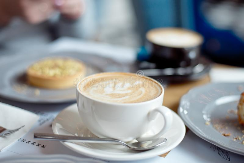 Close-up cup of coffee with pistachio tart on the table.  royalty free stock image