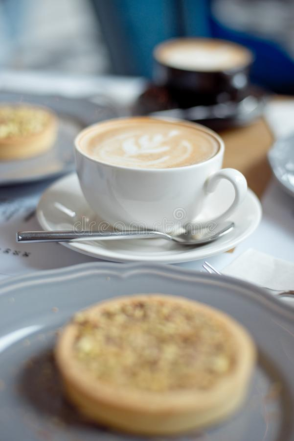 Close-up cup of coffee with pistachio tart on the table.  royalty free stock photography