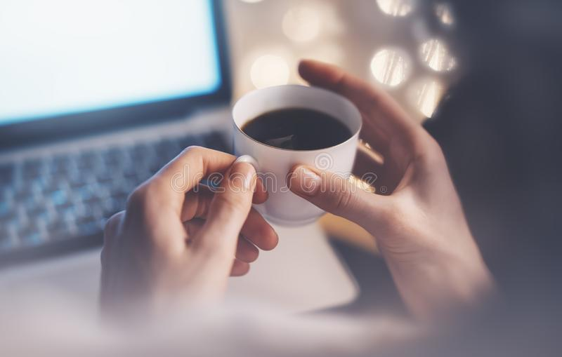close-up of a cup of coffee or tea in women hands on a light background bokeh and flare with an open laptop stock photography