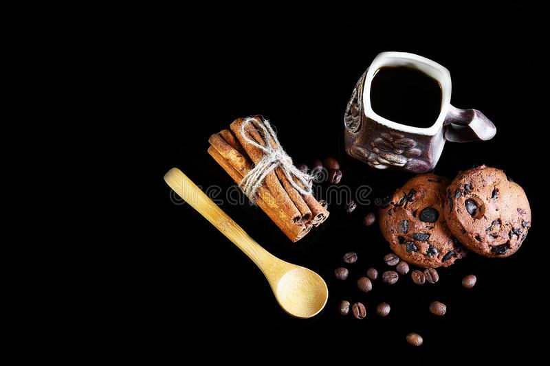 Close-up cup of espresso coffee, milk and spoon, round crunchy chocolate cookies with coffee beans, sticks of cinnamon on a black royalty free stock photography