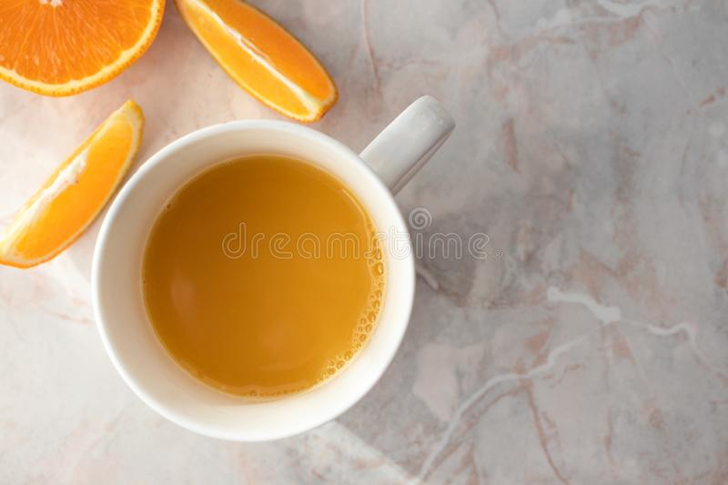 Close-up of cup of fresh homemade orange juice and cut oranges on table stock photography