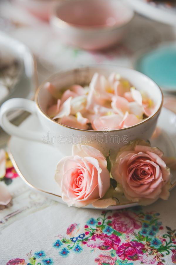 A close up of a cup with tea decorated with roses. Stands on a served table stock photography