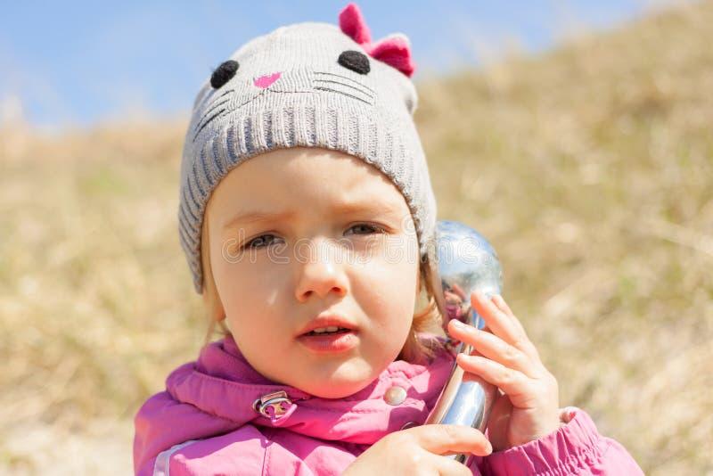 Close up curioso de fala da criança do telefone exterior fotografia de stock