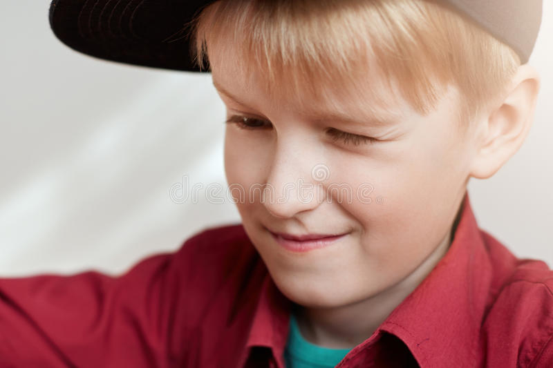 A close-up of curious little boy with white hair wearing stylish black hat and red shirt looking at something with narrowed eyes. stock photo