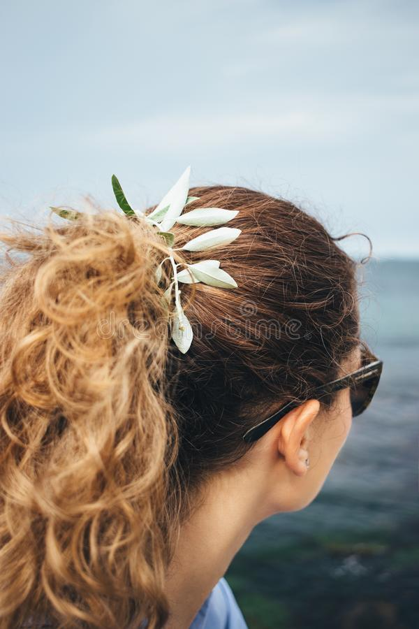 Close-up curly haired young woman with little stem stock photo