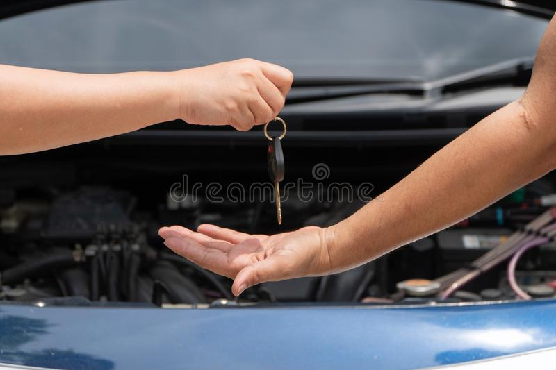 Close up of customer hand giving car key to car engine repairman on car engine background to repair it . Concept of maintenance ve stock image