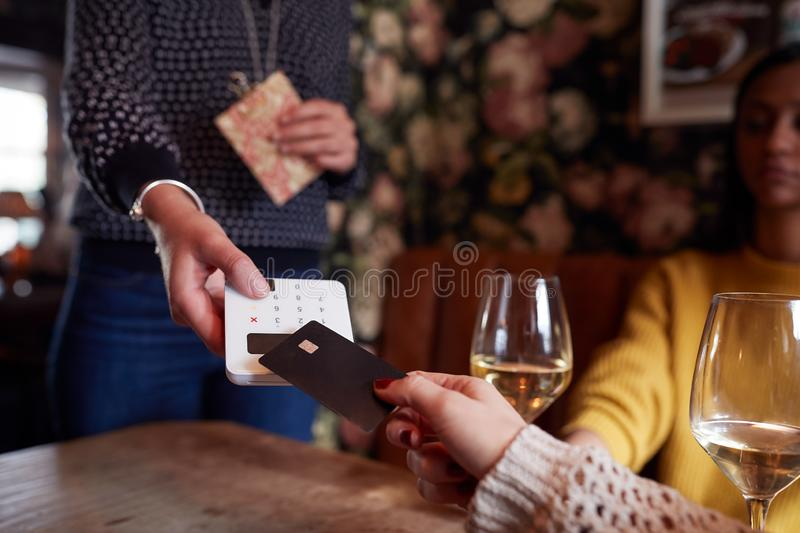 Close Up Of Customer Paying In Hotel Restaurant Using Contactless Card Reader stock image