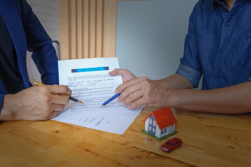 Close up of customer signing a paper document for buying house. Estate agent pointing finger showing where to sign on wooden desk royalty free stock image