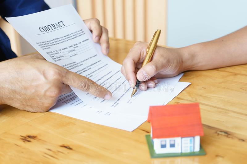Close up of customer signing a paper document for buying house. Estate agent pointing finger showing where to sign on wooden desk stock image