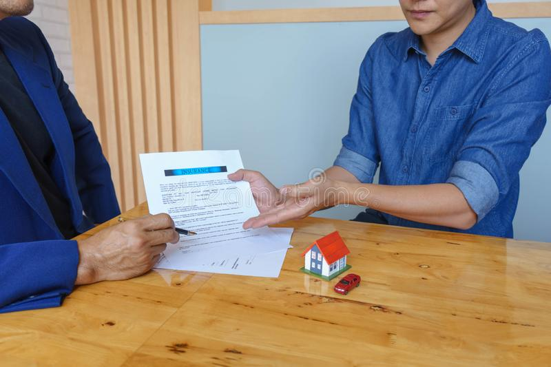 Close up of customer signing a paper document for buying house. Estate agent pointing finger showing where to sign on wooden desk. Real estate, home loan and royalty free stock photo