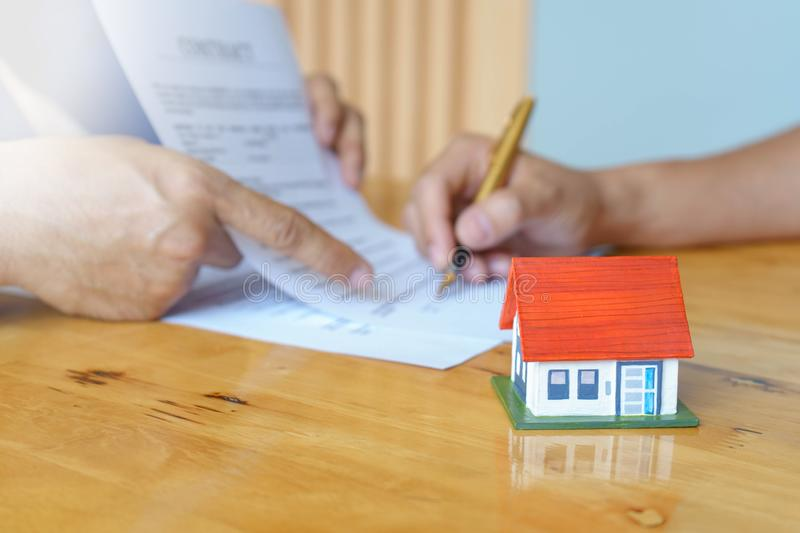 Close up of customer signing a paper document for buying house. Estate agent pointing finger showing where to sign on wooden desk stock photo
